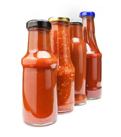 Čtyři kečup láhve izolovaných na bílém