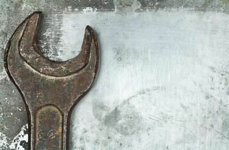 carpenter items: Old rusty wrench on metal background