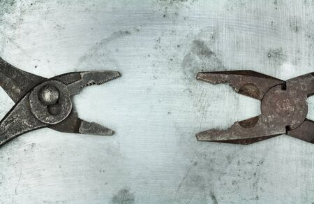 Pair of old pliers on metal background photo