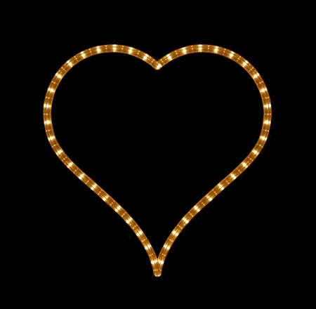 plastic heart: Glowing heart on black background Stock Photo