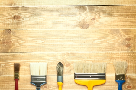 Different paintbrushes on a wooden background photo