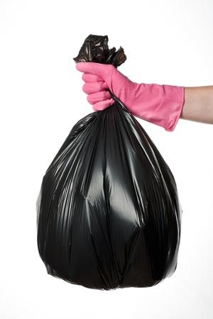 Hand in possesso di un sacchetto di immondizia di plastica nero pieno Archivio Fotografico