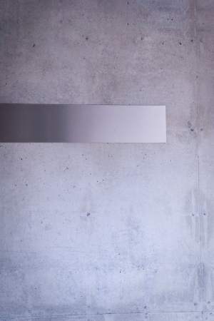 steel metal plate on concrete wall Stock Photo