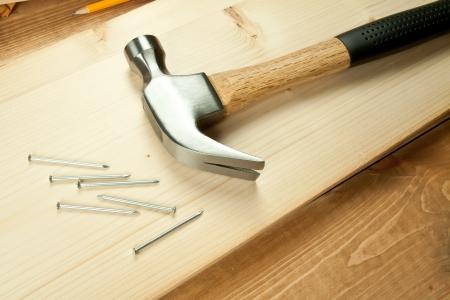 Kladivo a nehty na dřevěné pozadí.
