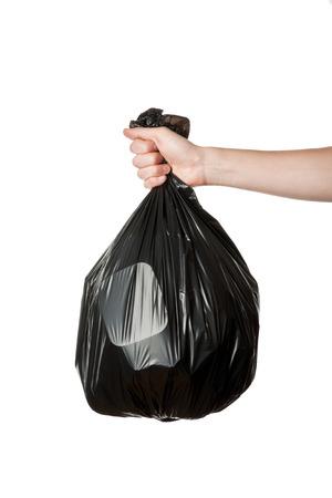 reciclar basura: Mano que sostiene una bolsa de basura de plástico negro completa