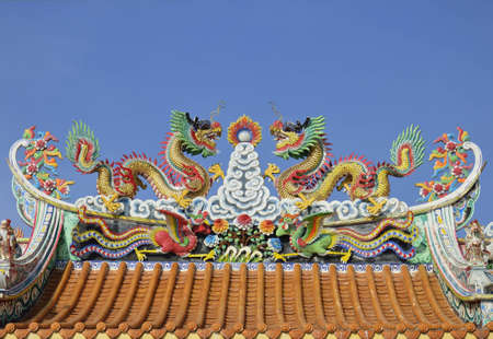 Statue of twin dragons on the roof of Chinese temple photo