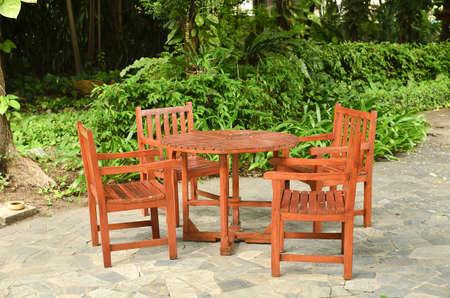 muebles de madera: Mesa y sillas de madera en un jardín exuberante