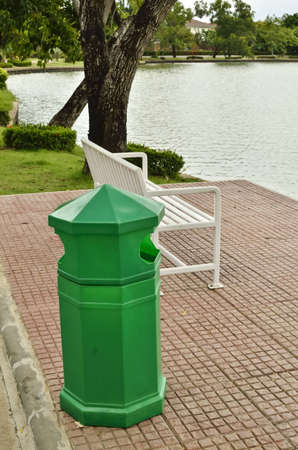 bench and recycle bin near a lake in public park photo