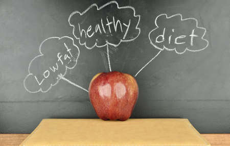 red apple on a book and beneficial of apple writing on blackboard Stock Photo