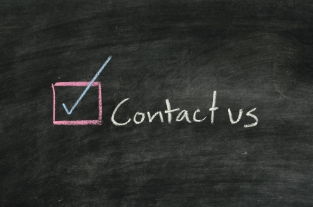 contact us and button written on blackboard Stock Photo