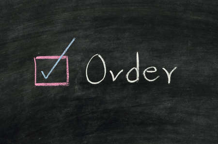 order and button written on blackboard Stock Photo