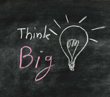 think big: the word think big and light bulb drawn on a chalk board,business concept