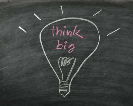 the word think big and light bulb drawn on a chalk board,business concept photo