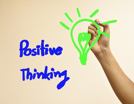 Male hand writing positive thinking and light bulb photo