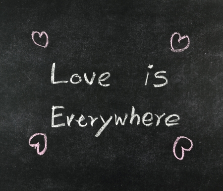love is everywhere written on blackboard photo