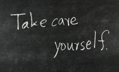 Take care yourself written on blackboard Stock Photo