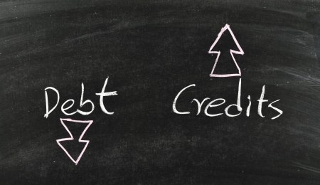 debt and credits concept written on blackboard