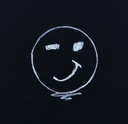 hand drawing smiley face on blackboard