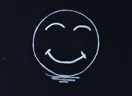 blackboard cartoon: hand drawing smiley face on blackboard