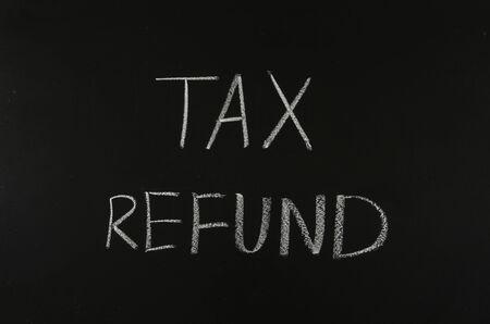 tax refund: writing word tax refund on blackboard Stock Photo