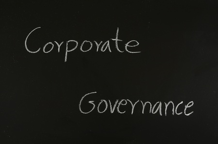 hand writing corporate governance on blackboard