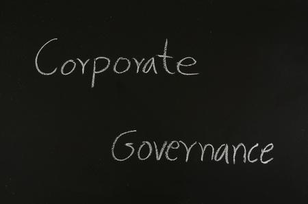 corporate governance: hand writing corporate governance on blackboard
