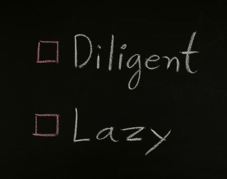 diligente: seleccione diligente o perezoso escrito en la pizarra Foto de archivo
