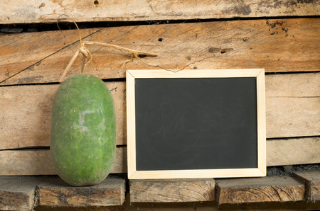 empty blackboard and fresh gourd on wooden wall background photo