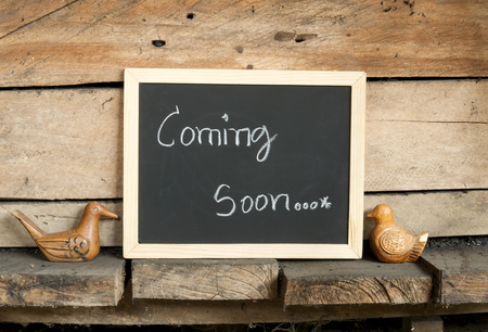 blackboard writing word coming soon on wooden wall background