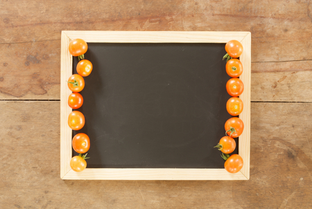 empty blackboard and fresh tomato on wooden wall background photo