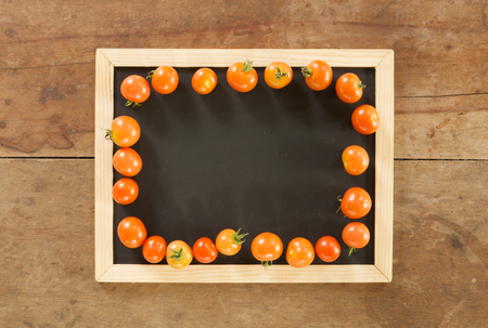 empty blackboard and fresh tomato on wooden wall background