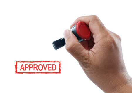 hand hold approved rubber stamp on white background photo