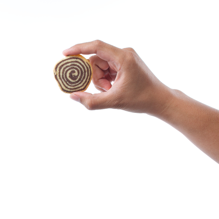 hand holding spiral cookie on white background