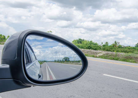 on mirrors: road and blue sky,rear view in car mirror