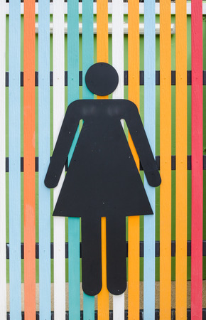 black steel women toilet sign on colorful wooden wall
