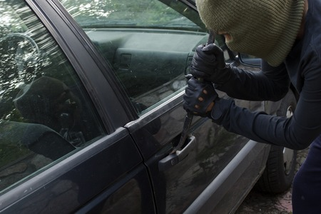 Car robbery in black gloves and mask breaking in car lock with crowbar tool Stockfoto