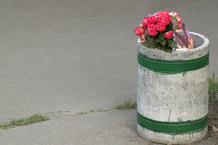 Beautiful bouquet of pink roses in the dustbin. Divorce concept with copy space