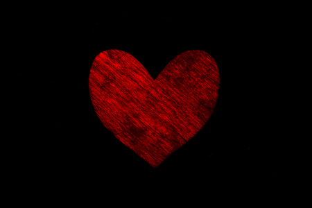Dark red painted wooden heart on a black background Foto de archivo