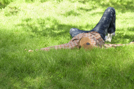 Young man lying and relaxing on a green grass in spring or summer