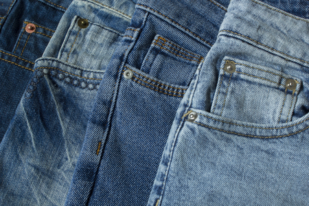 Blue jeans pants clothes pile background. Stack of blue jeans on shop desk close up