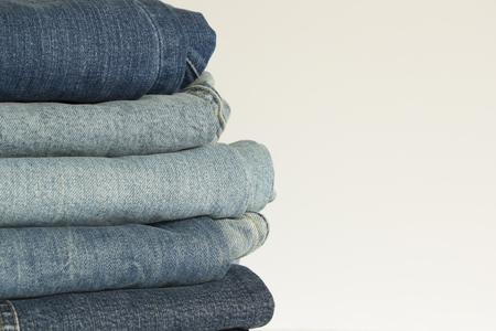 Pantalon en jean bleu nouveau tas de vêtements arrière-plan. Pile de jeans bleu sur fond blanc boutique Banque d'images
