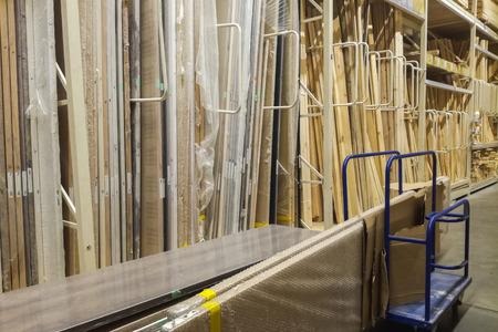 Holzstangen am Holzplatz des Baumarktes. Regal mit vorgeschnittenen Platten, Fräsholz, Abstellgleis, Sperrholz Standard-Bild