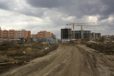 Unfinished building construction against already built houses. View from far. Building concept