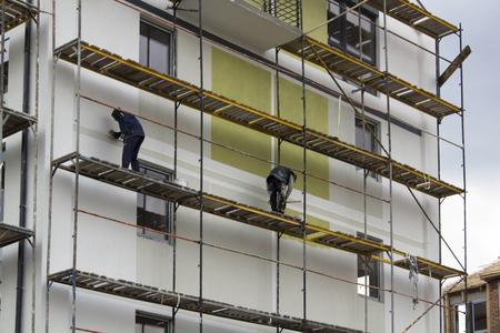 Vista del patio del edificio desde lejos con dos trabajadores en un andamio