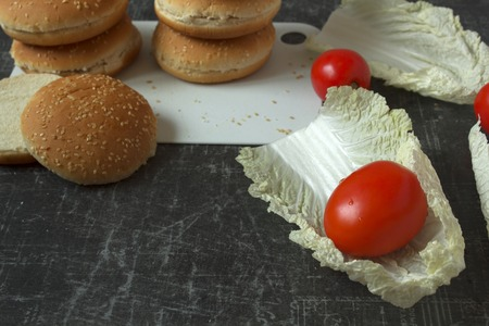 Fresh tomatoes, lettuce and burger buns with sesame seeds on a chopping board. Copy space