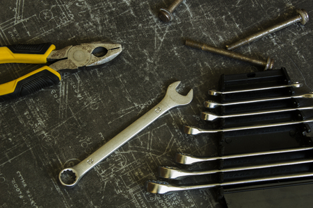 Tool set of pliers, different wrenches, bolts and nuts on abstract grey surface