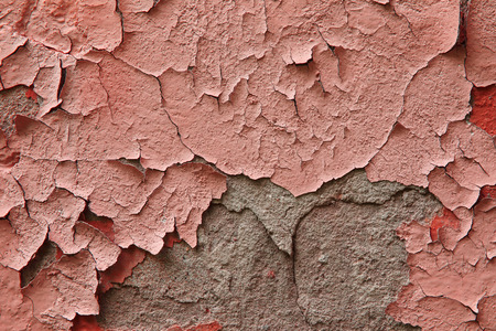 Close up fragment of an old exterior wall with cracked peeling plaster pink color