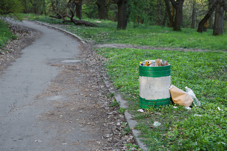 overflowing green garbage bin in park and trash near it