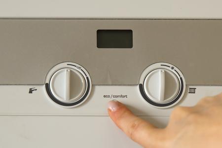 Main de femme appuyer sur un bouton d'installation de la chaudière de chauffage au gaz domestique se bouchent Banque d'images