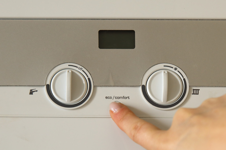 Woman hand push an installation button of home gas heating boiler close up